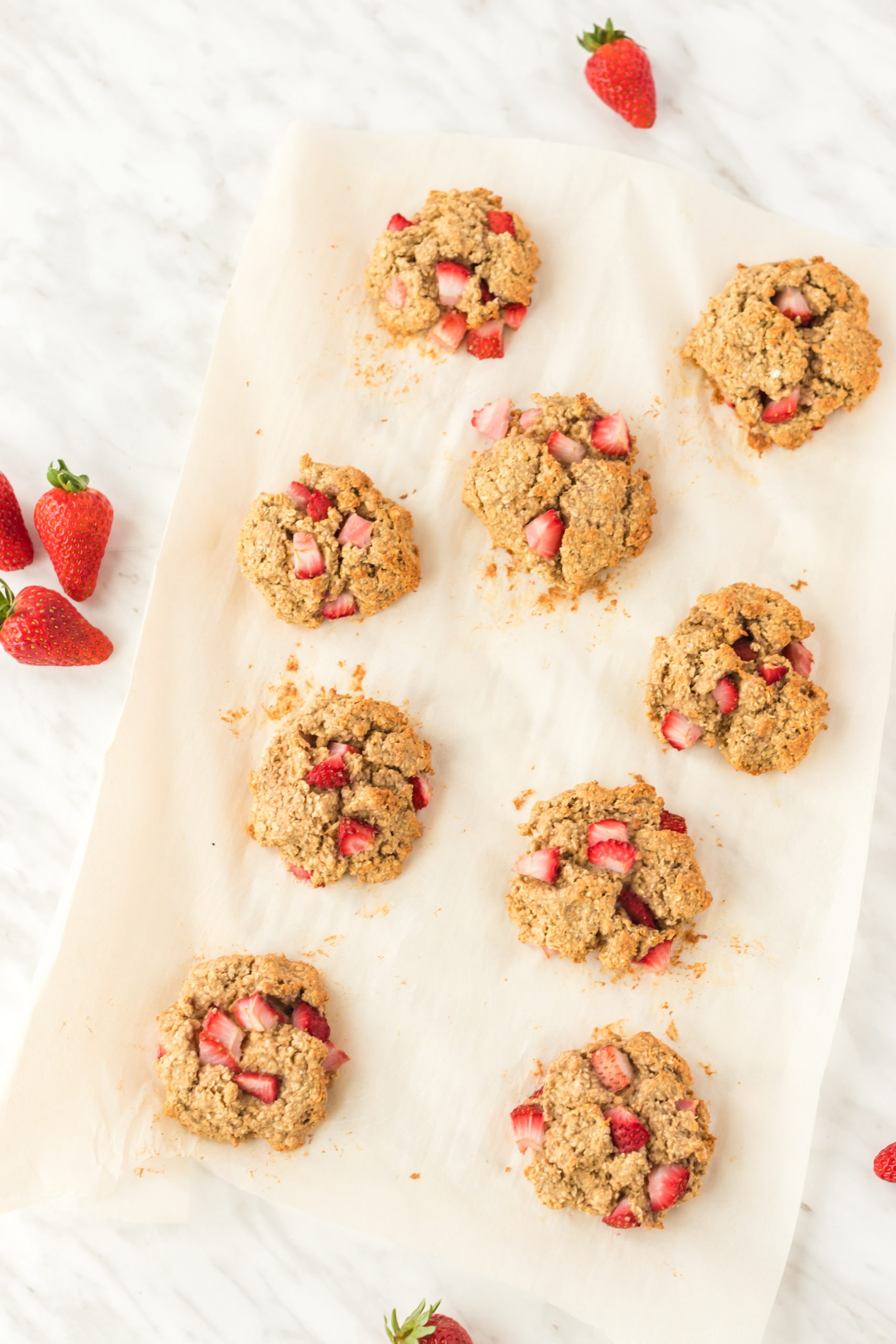 berry scuffins spread out on parchment paper with fresh strawberries