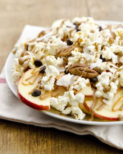 Apple Nachos: sliced apples topped with a date-sweetened caramel, chocolate chips, nuts, and popcornth
