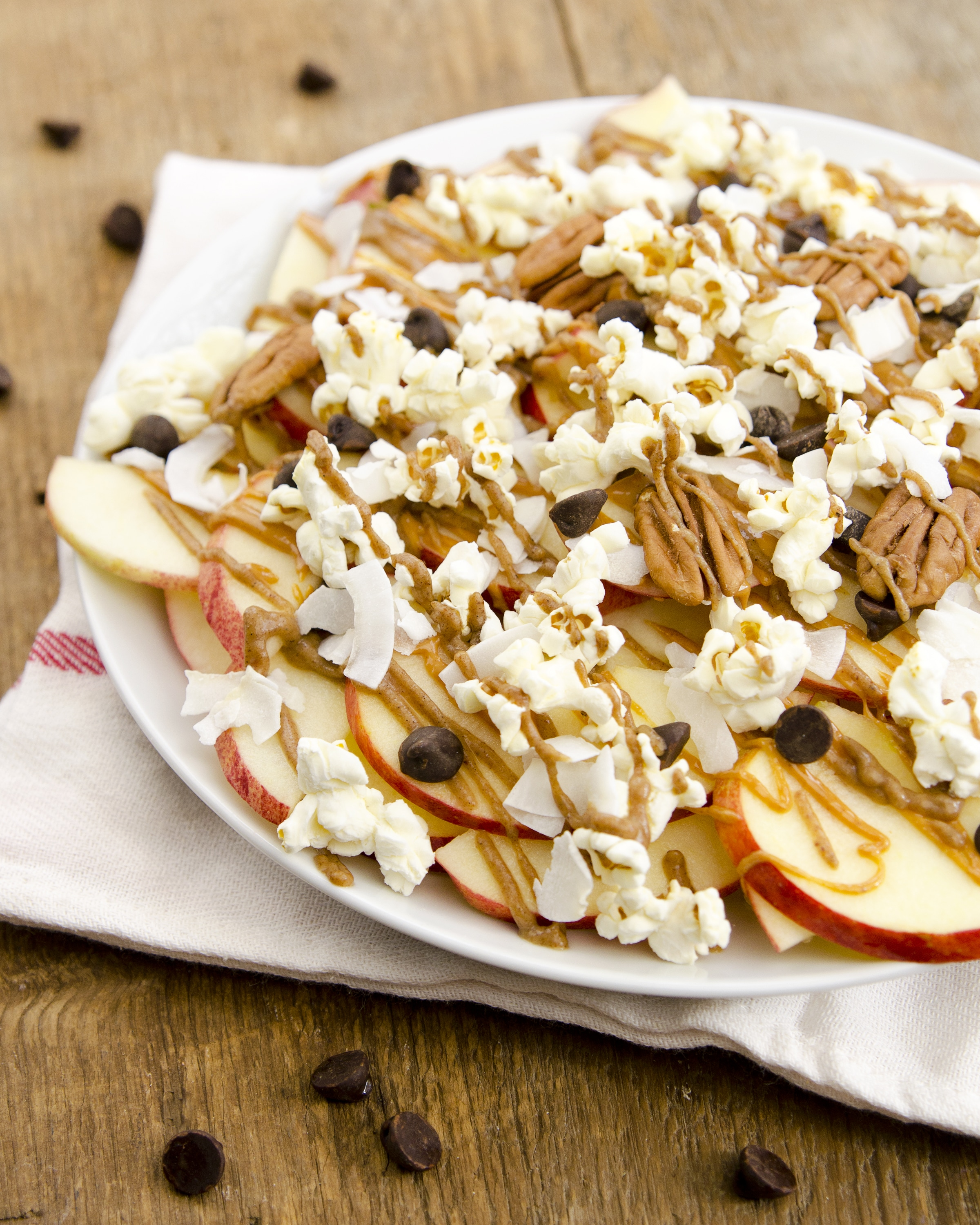 sliced apples topped with a date-sweetened caramel, chocolate chips, nuts, and popcorn