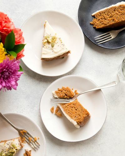 Three slices of Vegan Carrot Cake plated, with a vase of colorful flowers