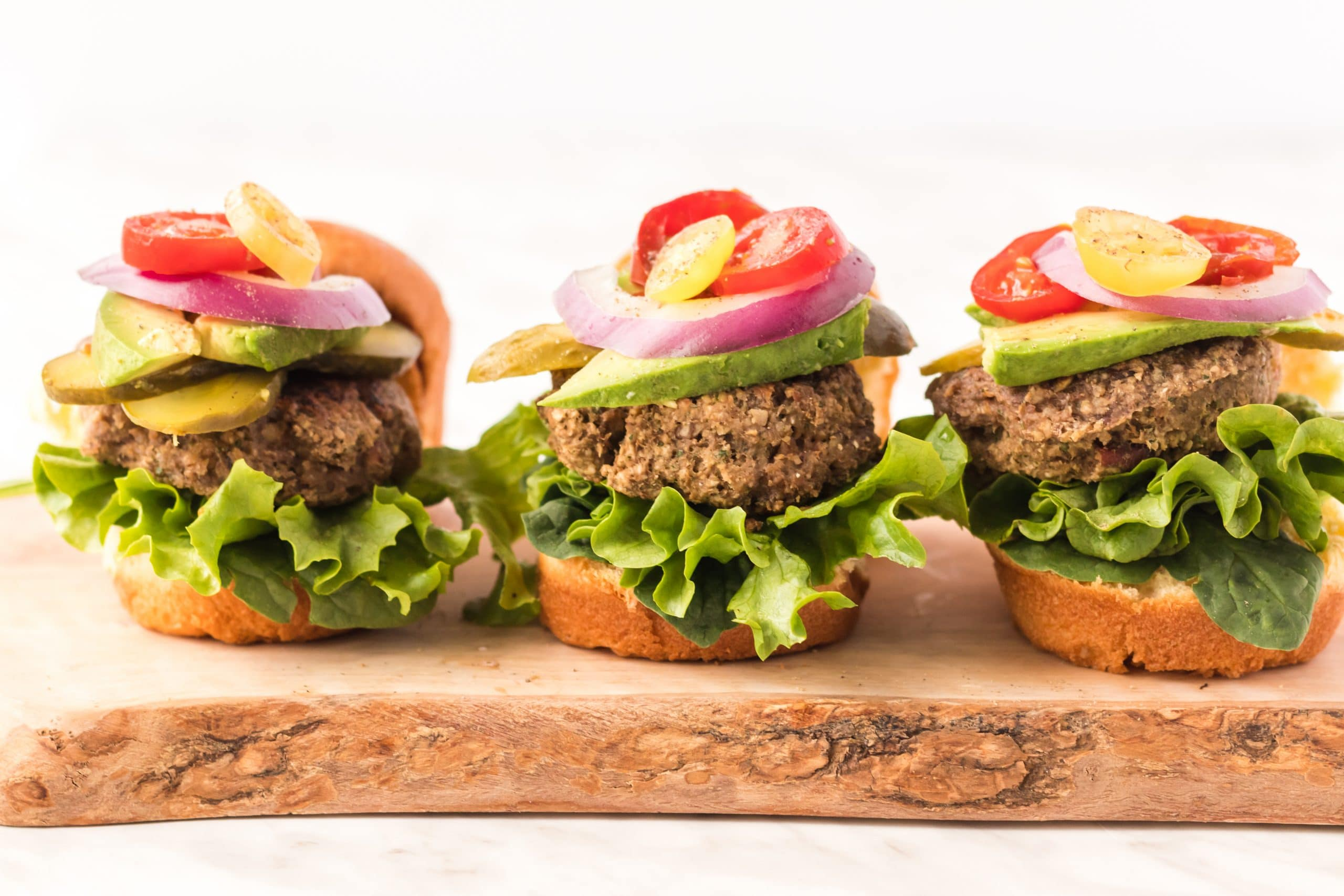 three veggie burgers with lettuce, onion, tomatoes, and avocado