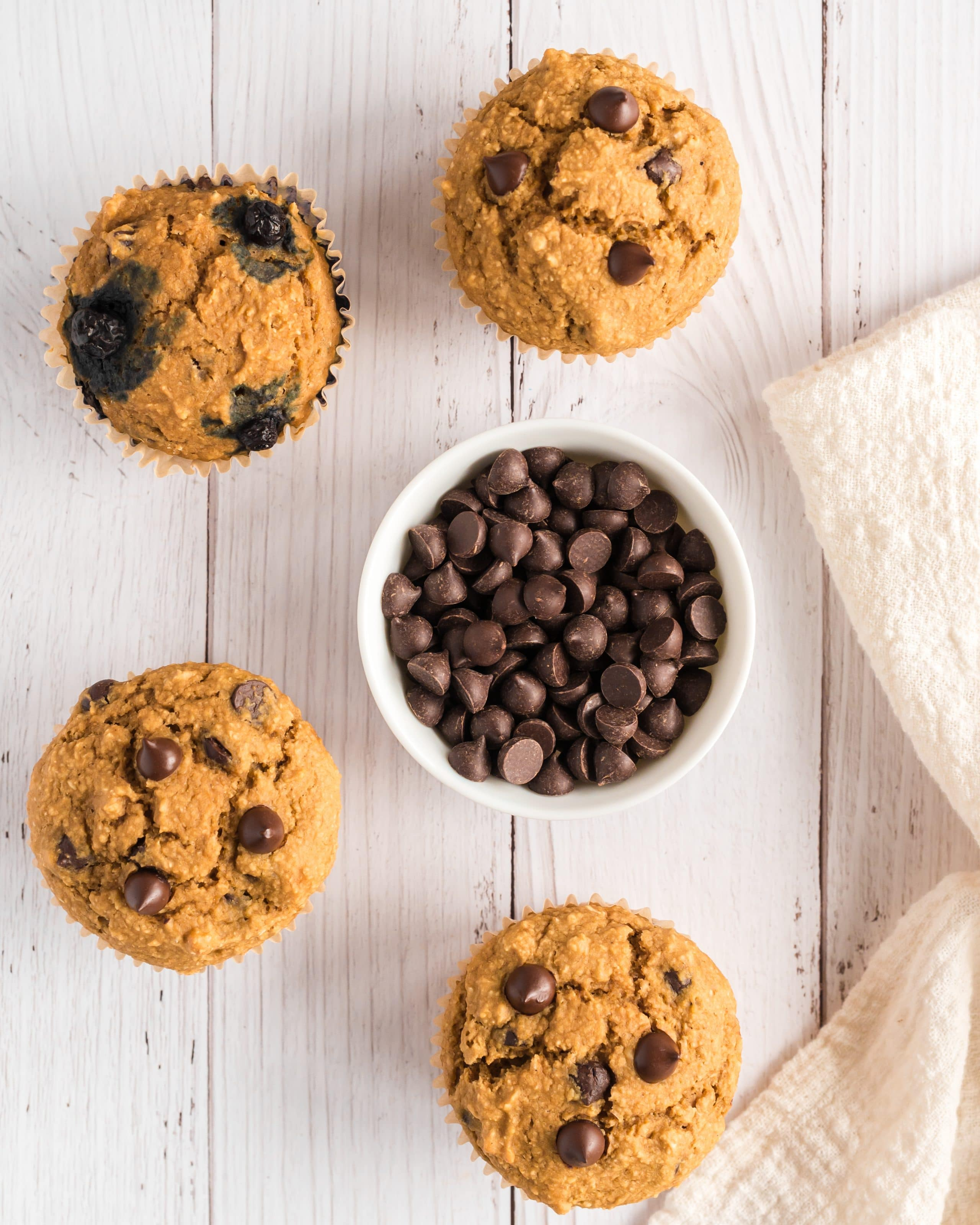muffins (some with blueberries) on table surrounding bowl of chocolate chips