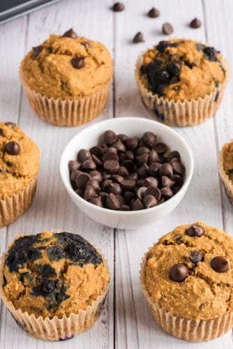 vegan chocolate chip muffins (some with blueberries) on table surrounding bowl of chocolate chips