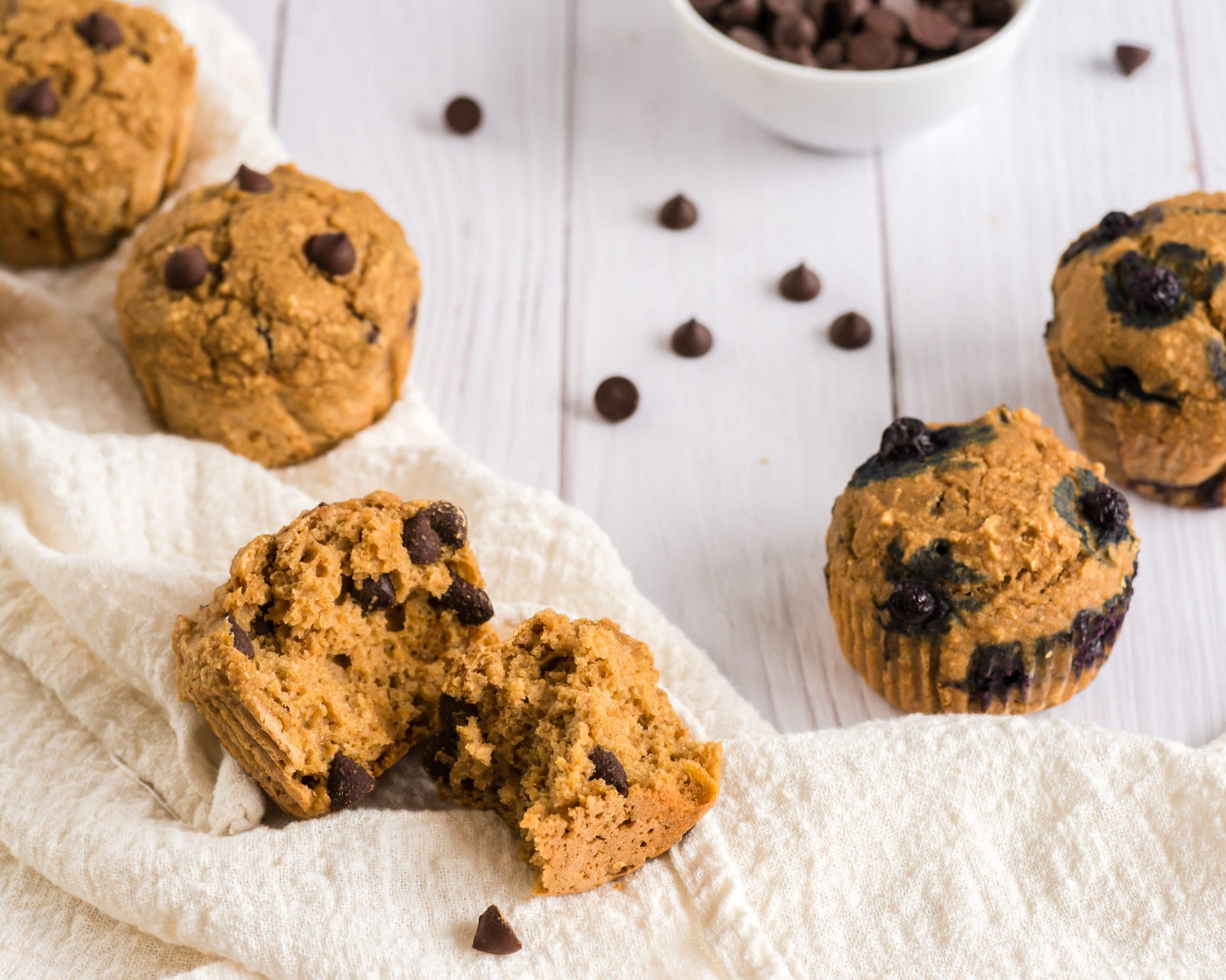 vegan chocolate chip muffins on table, one broken open