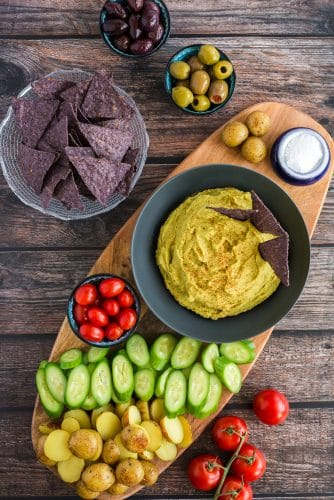 Green Pea Hummus on cutting board surrounded by fresh vegetables and tortilla chips