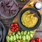 Green Pea Hummus in bowl surrounded by chips and vegetables