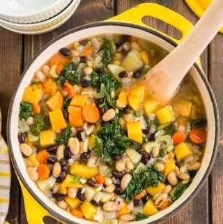 Large pot of pantry soup, containing beans, vegetables, greens and with wooden spoon in soup pot