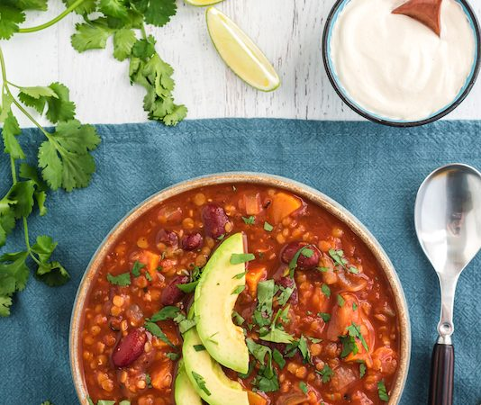 sweet potato lentil chili served with avocado slices