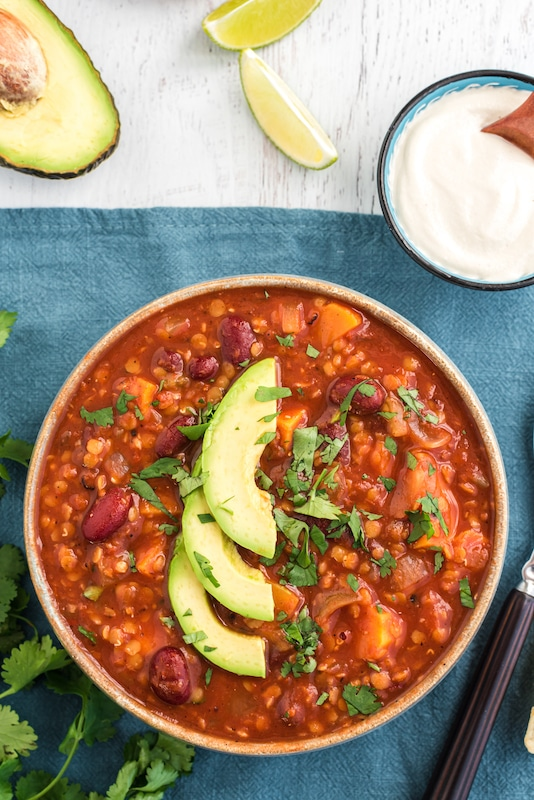 bowl of sweet potato chili with sliced avocado on top
