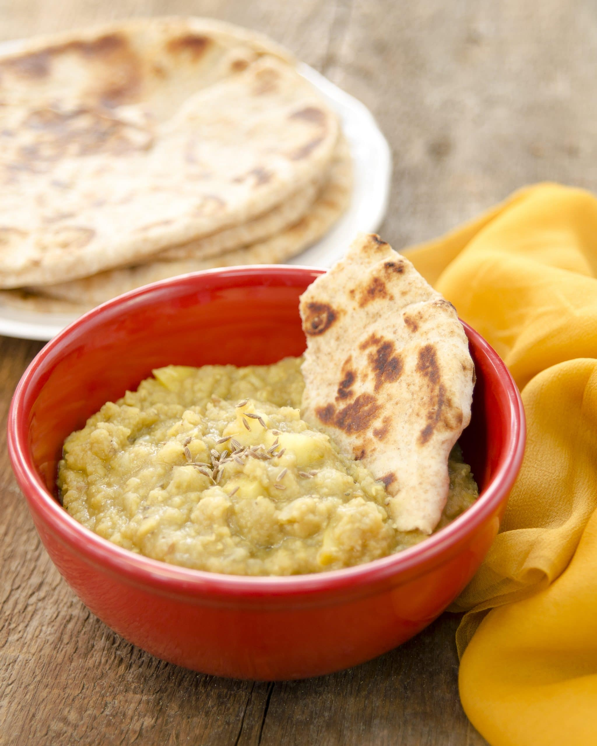 Apple Lentil Dal served in bowl with roti bread on the side.