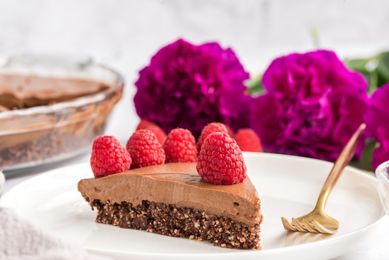 front view of sliced chocolate pie, flowers in back