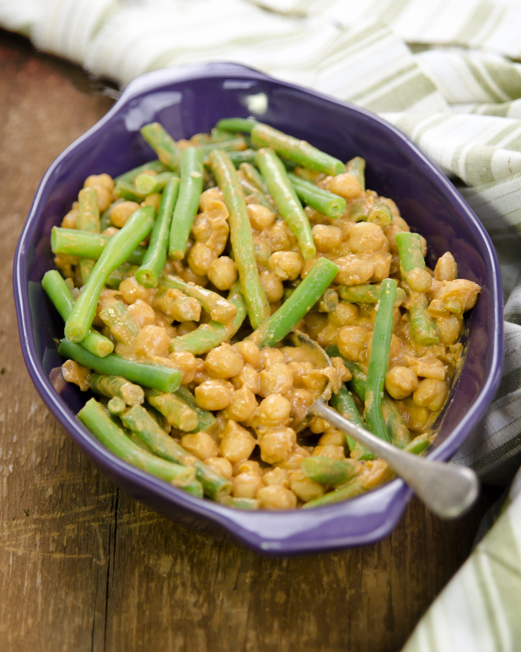 Saucy Chickpeas & Green Beans in Casserole Dish with Serving Spoon