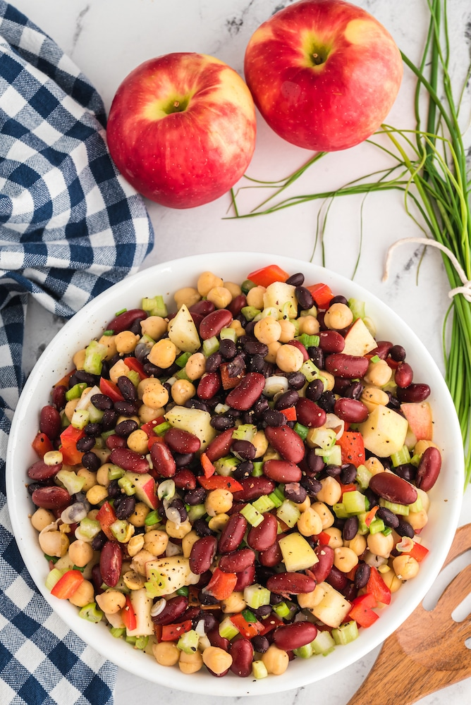 three bean salad in a serving bowl with two apples
