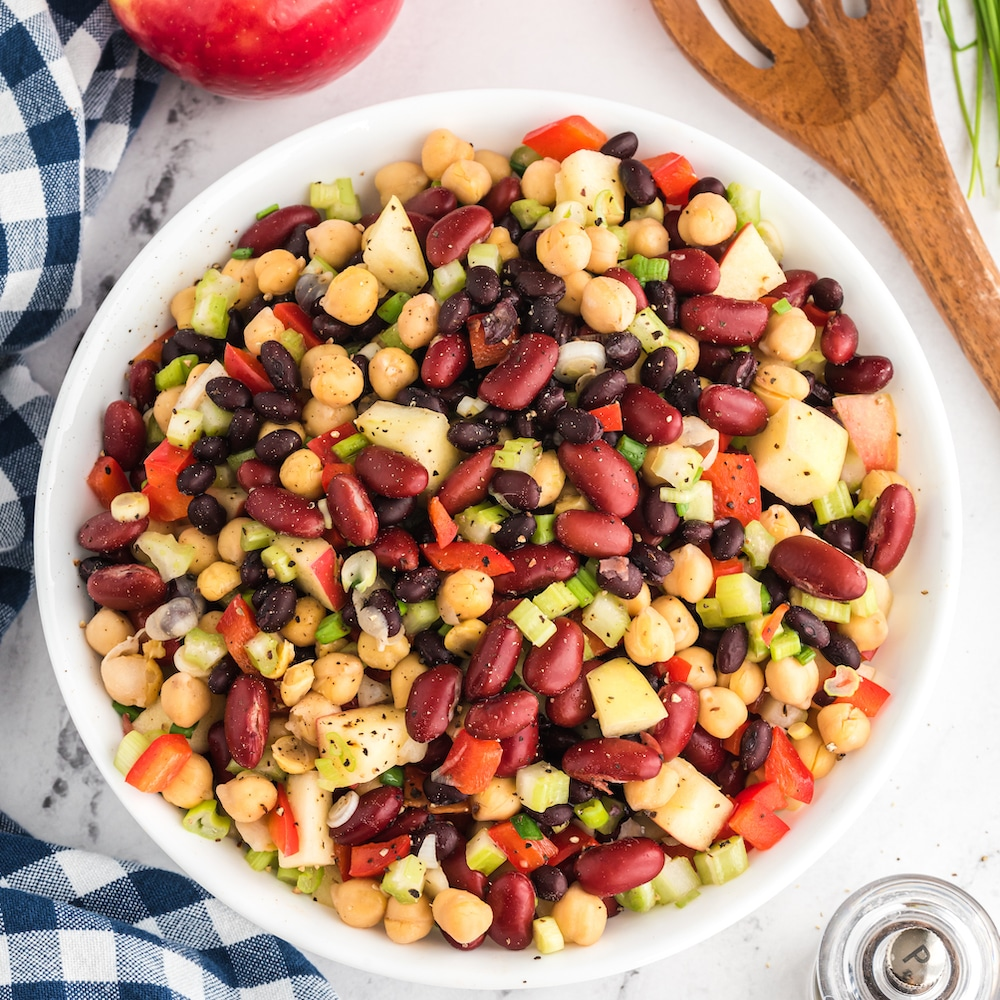 bowl of three bean salad with wooden spoon