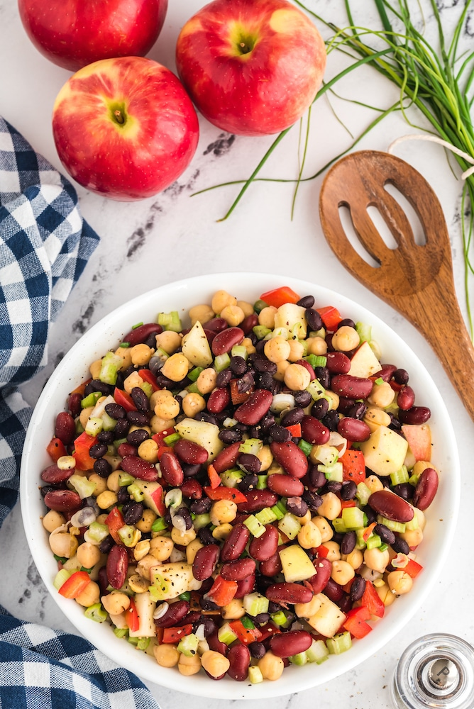 three bean salad in a bowl with three apples and wooden spoon