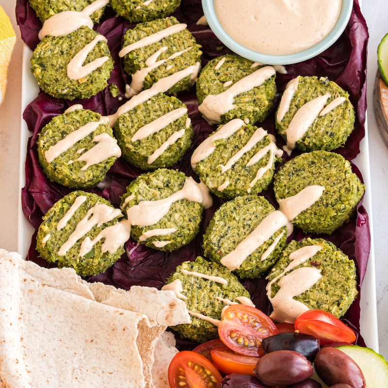 plate of green chickpea falafels tahini sauce drizzled on top