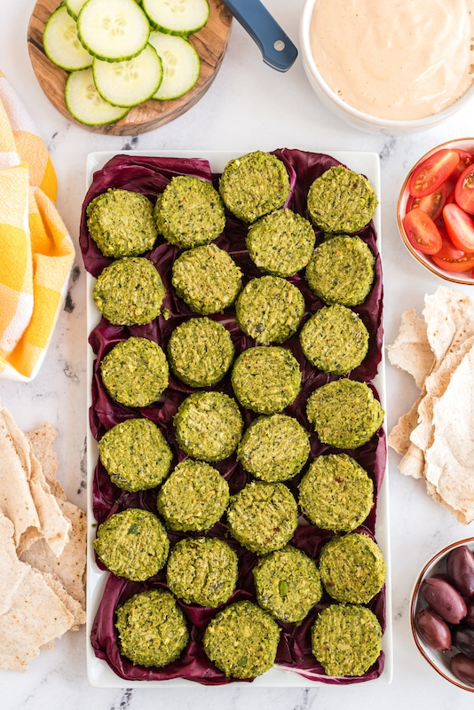 plate of green chickpea falafels with pita bread and sliced tomatoes and cucumbers