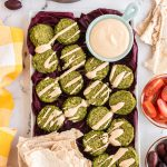 Green Chickpea Falafels on a tray drizzled with smoky tahini sauce